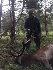 Der erfolgreiche Erleger im Morgengrauen an seinem Hirsch